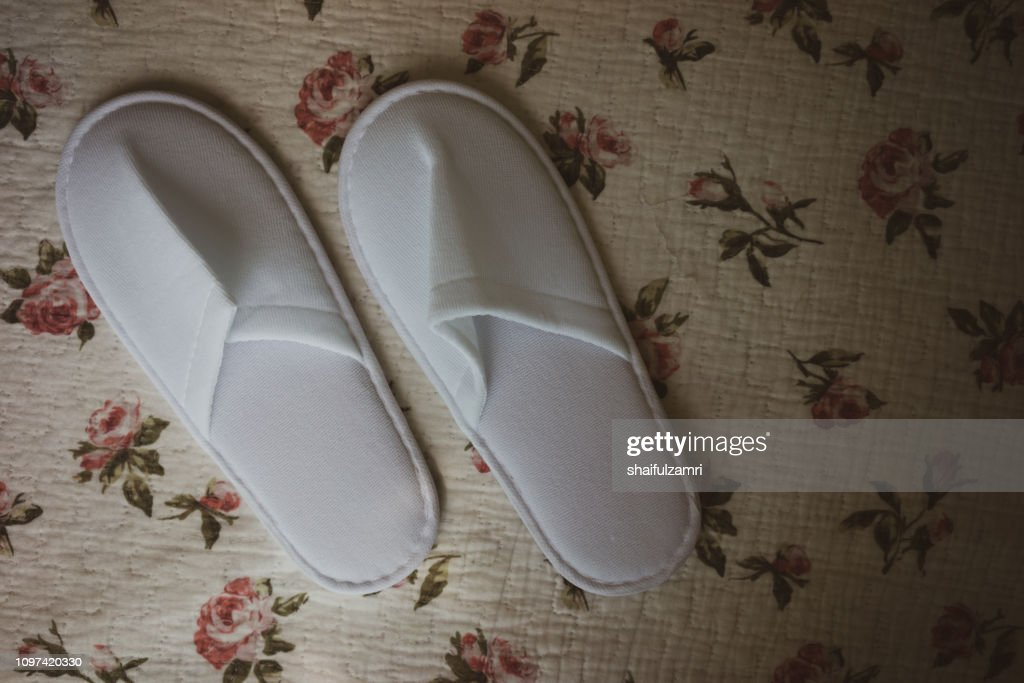 White towelling hotel disposable slippers over old and rust bed-sheet : Stock Photo