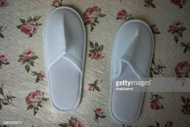White towelling hotel disposable slippers over old and rust bed-sheet