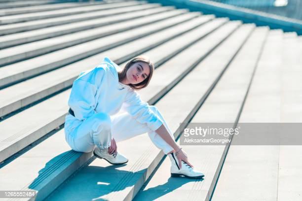 traje de chándal blanco mujer sentado en los escalones - white pants fotografías e imágenes de stock