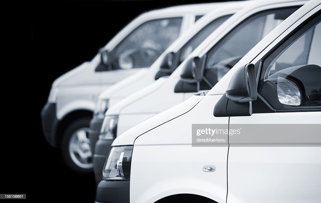 White transporters / vans in a row on black background : Stock Photo