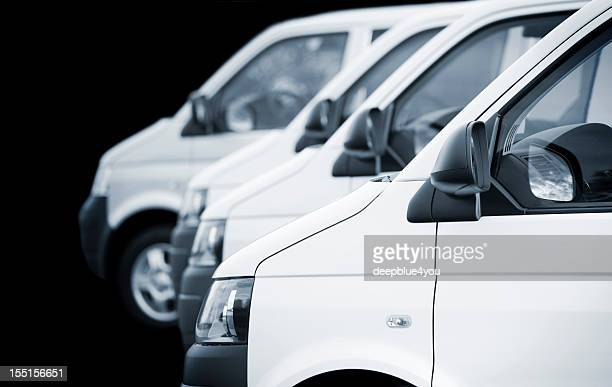 white transporters / vans in a row on black background - van stock pictures, royalty-free photos & images