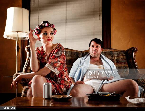 white trash series: couple sitting on their couch - wife photos stock photos and pictures
