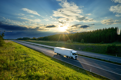 White truck driving on the highway in the countryside in the rays of the sunset with dramatic clouds 949596036