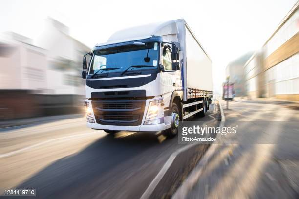 white truck in motion uk street - uk stock pictures, royalty-free photos & images
