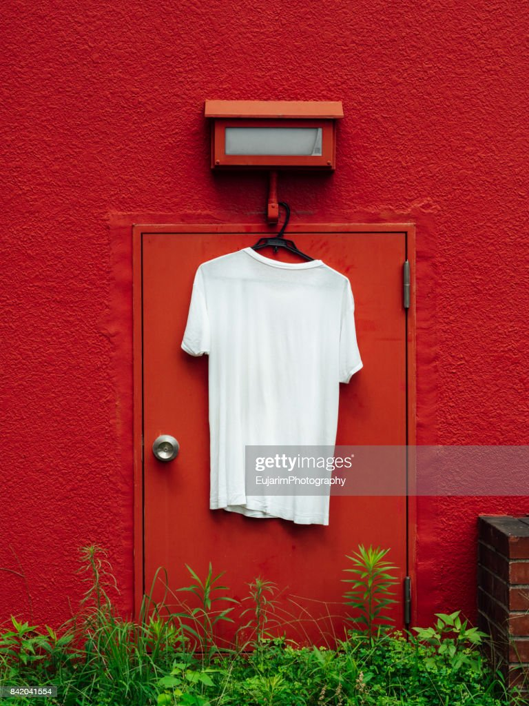 White T-shirt hangs on the red wall : Stock Photo