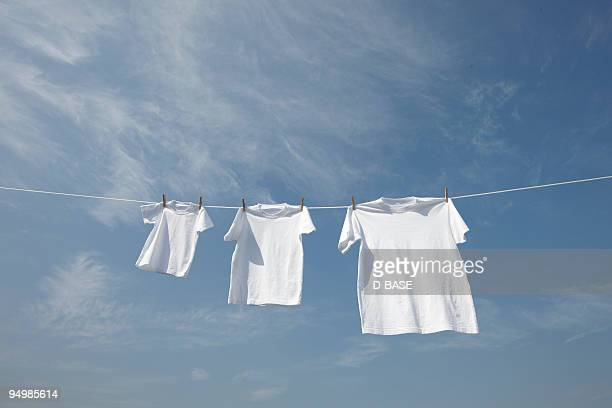 White t-shirts in a row on washing line.
