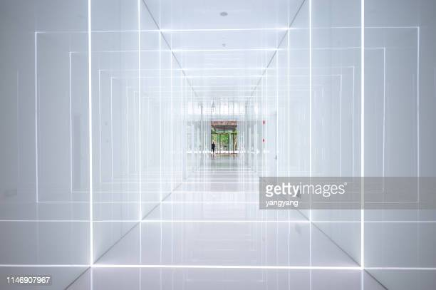white tunnel in an indoor empty architectural space - fluchtpunkt stock-fotos und bilder
