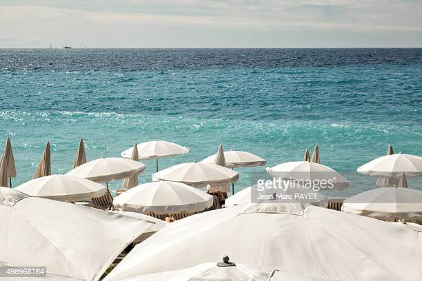 white umbrellas on the beach in nice - jean marc payet stockfoto's en -beelden