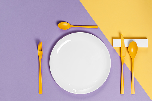 White utensils and yellow cutlery on a pastel colored background. Colors in the style of pop. 904834084