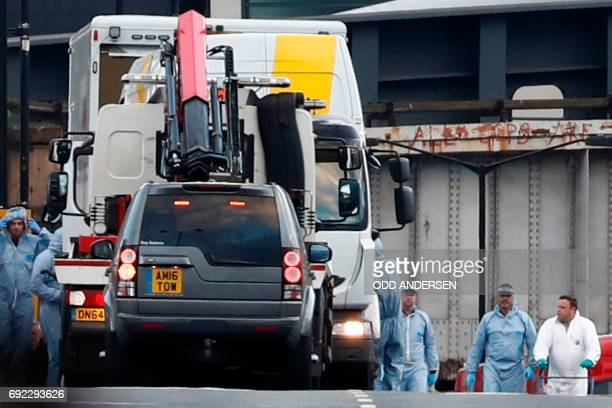 A white van used in the attack on London Bridge is seen being loaded into another van by the police as forensics officers work on London Bridge in...