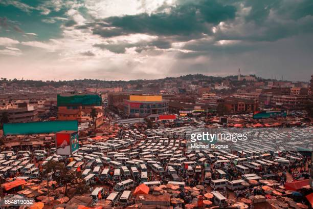 white vans and buses jockey for position at a depot in kampala, uganda, seen in abstract colors of teal and orange. - kampala stock pictures, royalty-free photos & images