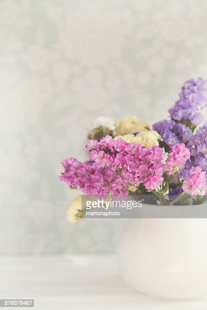 White vase with pink, yellow and violet flowers