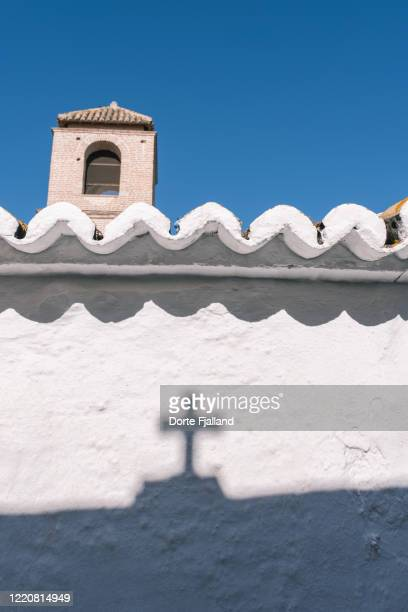 white wall with a shadow with a cross. behind a tower and a blue sky - dorte fjalland stock-fotos und bilder