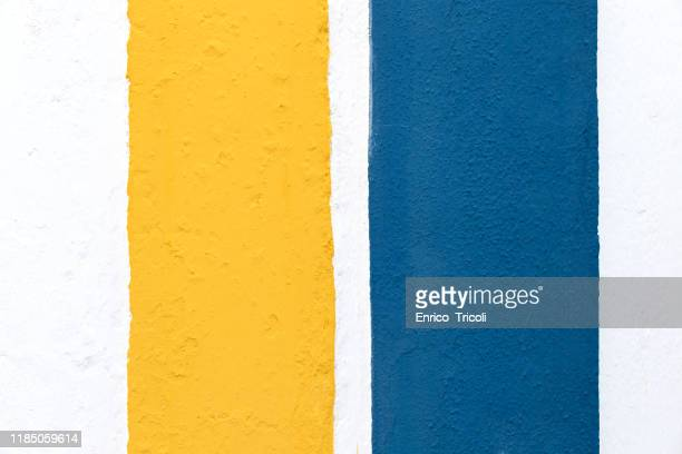 white wall with two coloured strips of blue and yellow paint. background, texture. - sports uniform stock pictures, royalty-free photos & images