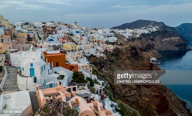 White washed villas adorn the cliffs of the village of Oia on the northwestern tip of the Greek island of Santorini in the Aegean Sea on May 20 2020...