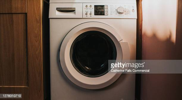 white washing machine in a utility room - washing machine stock pictures, royalty-free photos & images
