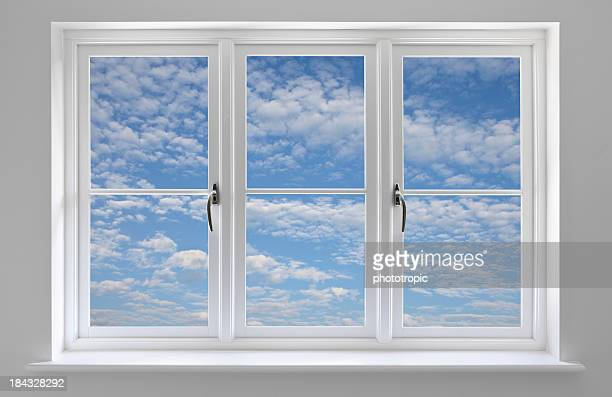 White window with blue sky and wispy clouds