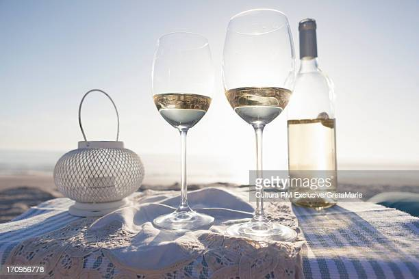 White wine, glasses and candle on beach