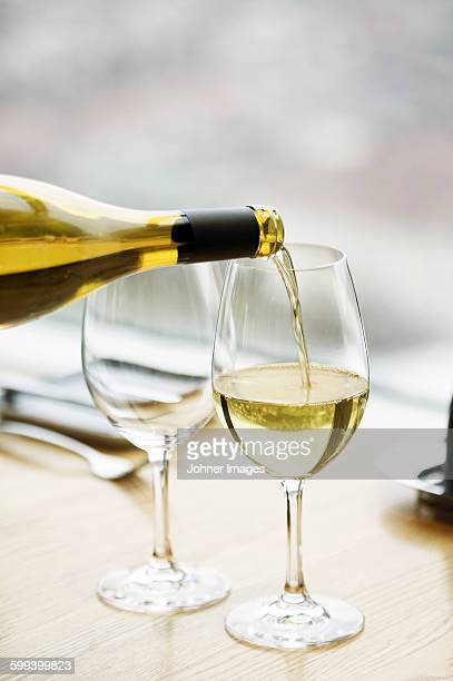 White wine is pouring into wineglass