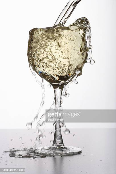 White wine overflowing from glass