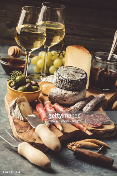 white wine with charcuterie assortment on the stone background - charcuteria fotografías e imágenes de stock