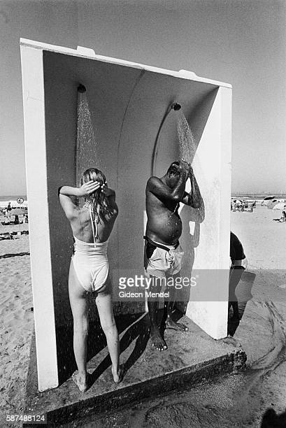 A white woman and black man share a beach shower in Durban South Africa at a time when apartheid racial barriers are being challenged South Africa...