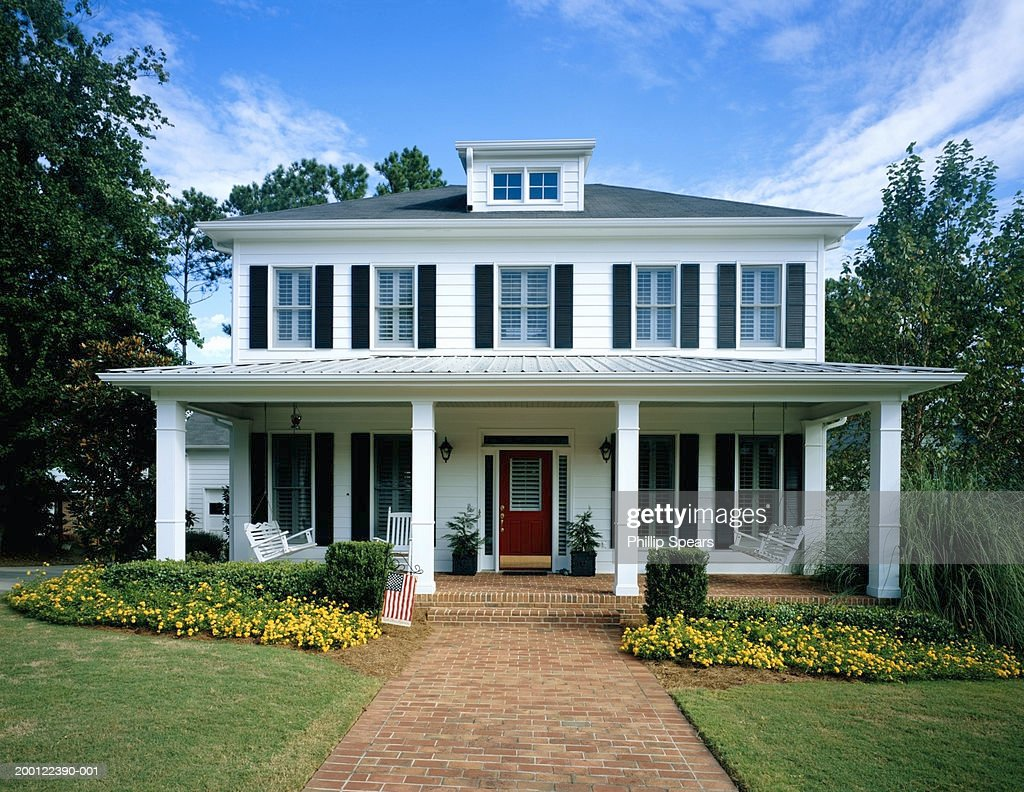 White wooden house, flowers blooming around front porch : Stock-Foto