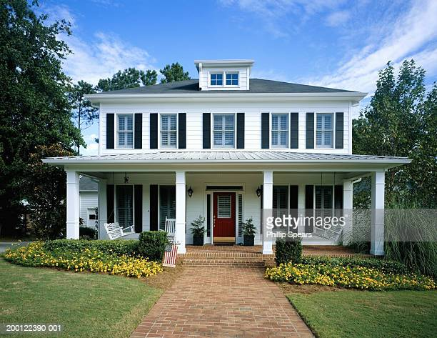 white wooden house, flowers blooming around front porch - frontaal stockfoto's en -beelden