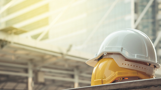 white, yellow hard safety helmet hat for safety project of workman as engineer or worker, on concrete floor on city 843513390