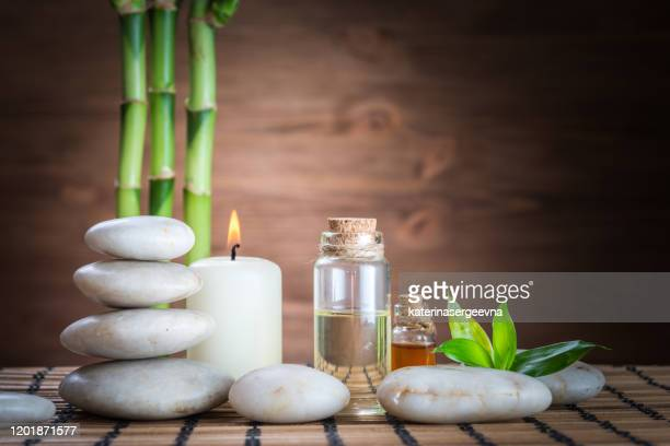 white zen balance stones, an orchid flower, a bamboo plant and a candle on a wooden table - aromatherapy stock pictures, royalty-free photos & images