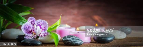 pierres d'équilibre zen blanches, une fleur d'orchidée, une usine en bambou et une bougie sur une table en bois - karesansui photos et images de collection
