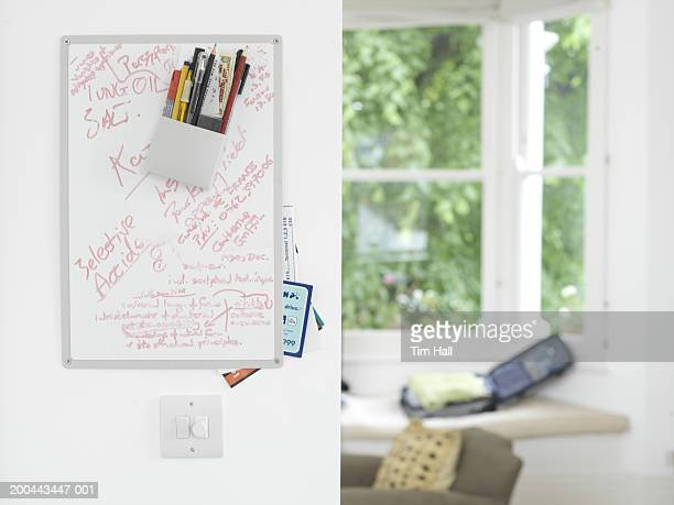 Whiteboard covered in notes, suitcase in window alcove