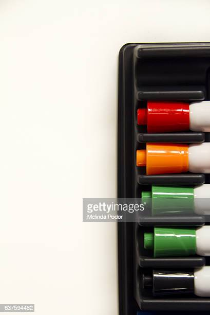 whiteboard markers attached to whiteboard