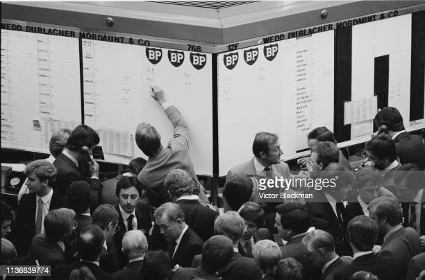 White-collar workers at the London Stock Exchange near the BP and Wedd Durlacher Mordaunt & Co boards, UK, 26th September 1983.