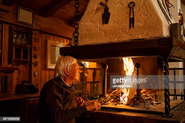 White-haired senior man enjoys, makes fire in the fireplace  Chalet