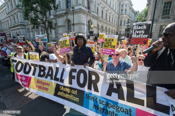 Whitehall is blocked as supporters of Stand Up To Racism take the knee at Downing street to support black England players racially abused after the...
