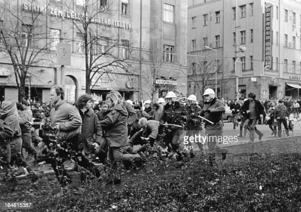 Whitehelmet Czechoslovakian riot policemen run forward in unison each holding a baton with their hands thrust forward 28 October 1988 at Wenceslas...