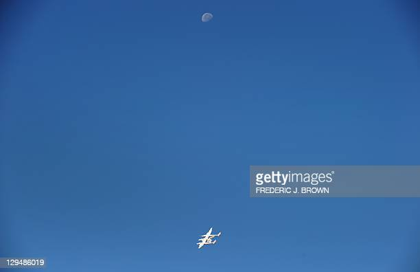 WhiteKnightTwo, carrying SpaceShipTwo, takes flight over Spaceport America, flying beneath the moon northeast of Truth Or Consequences, on October...