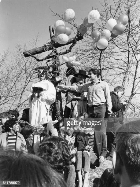 A whiterobbed 'preacher' reads to a crowd of young attendees at the 'Easter BeIn' on a rock in Central Park New York New York March 26 1967