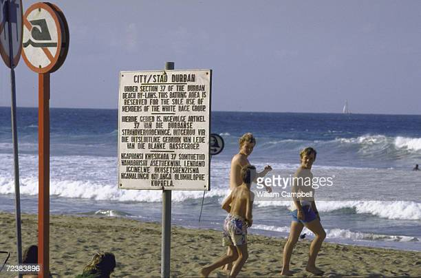 Whites only sign in foreground at restricted beach with bathers in background