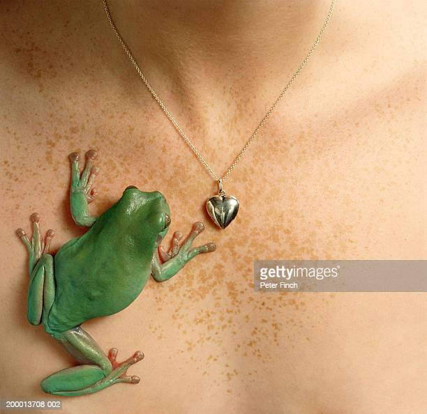 White's tree frog  on young woman's chest by locket, close-up