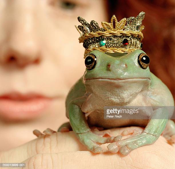 white's tree frog wearing crown, resting on woman's hand, close-up - fairytale stock pictures, royalty-free photos & images
