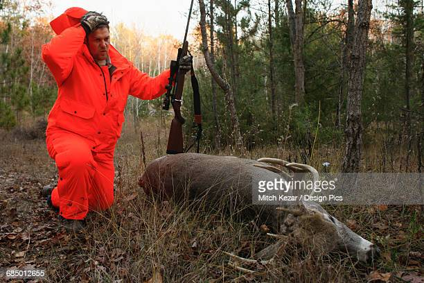 whitetail deer hunter stops to rest while dragging dead deer - dead deer stock photos and pictures