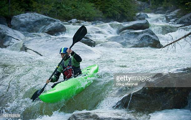 A whitewater kayaker continues down a rocky section of a high moutain river.