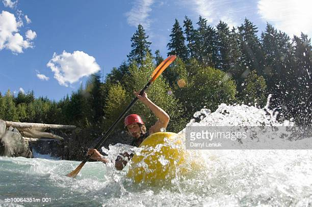 Whitewater kayaker paddling rapids in river