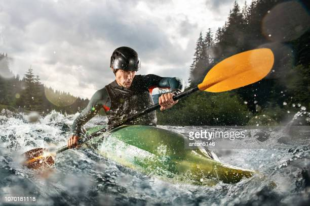 whitewater kayaking, extreme kayaking. a guy in a kayak sails on a mountain river - kayak stock pictures, royalty-free photos & images