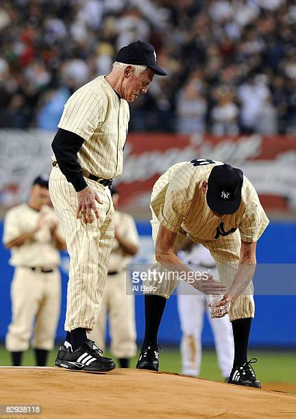 Whitey Ford and Don Larsen scoop up dirt from the mound during a pregame ceremony prior to the start of the last regular season game at Yankee...