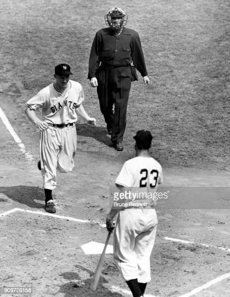 Whitey Lockman of the New York Giants is greeted by Bobby Thomson after hitting a homerun as umpire Art Gore looks on during an MLB game against the...