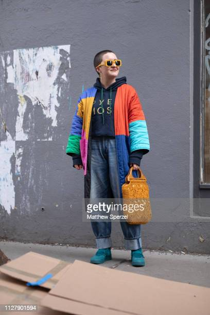 Whitney Bauck is seen on the street attending Bode during Men's Fashion Week New York wearing colorful coat with black hoodie copper bag and blue...