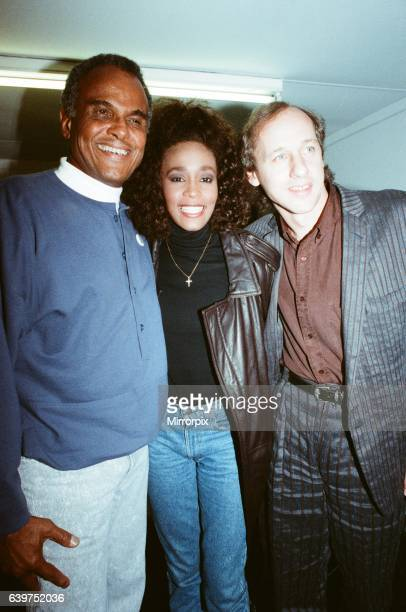 Whitney Houston smiling backstage at the Nelson Mandela concert in London with Harry Belefonta and Mark Knopler on 11th June 1988